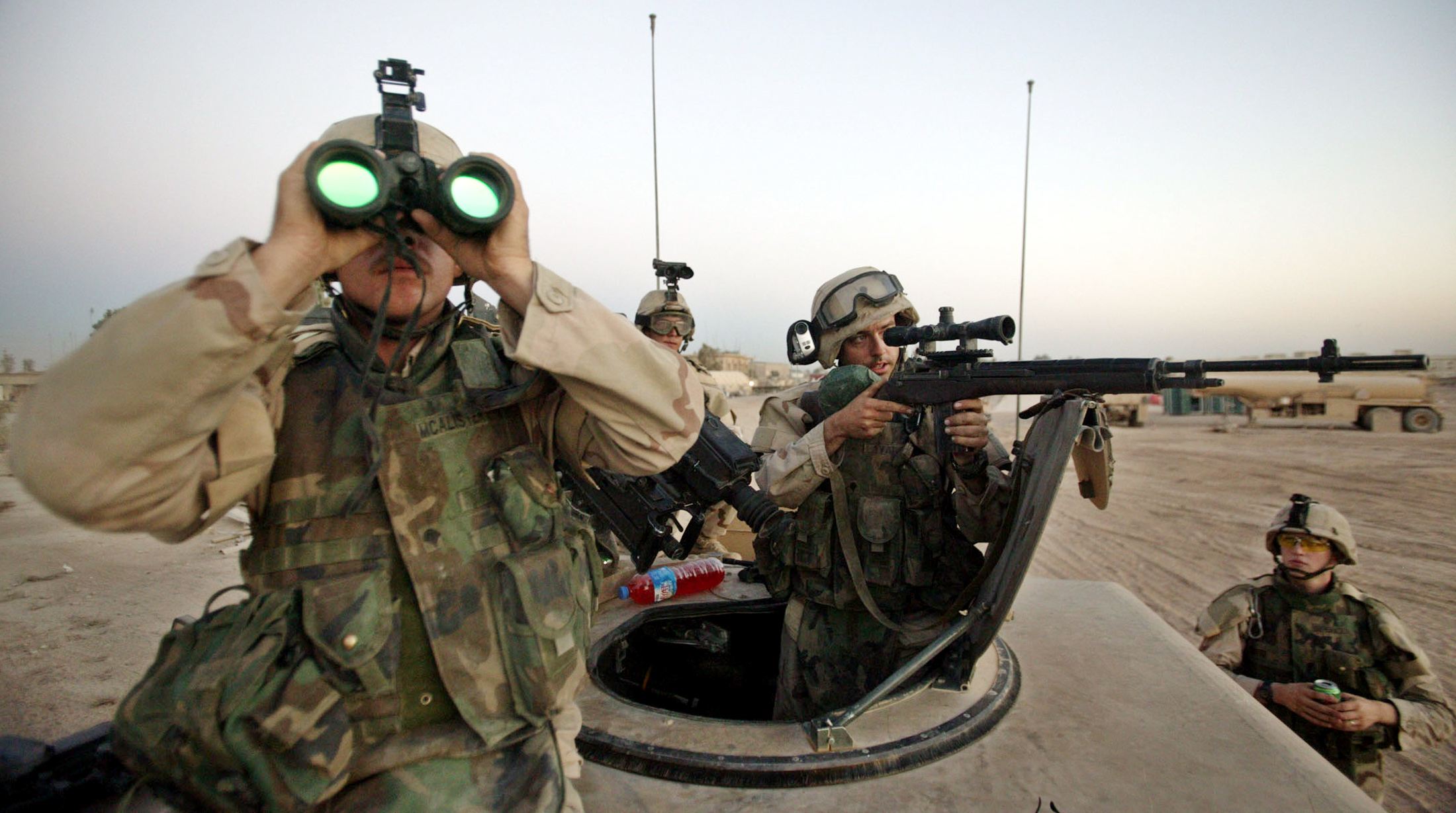 A U.S. Army sniper takes aim at a suspected enemy observer at Camp Eagle in the Baghdad suburb of Sadr City on Aug. 16, 2004. Photo by David P. Gilkey/ Pool via Reuters