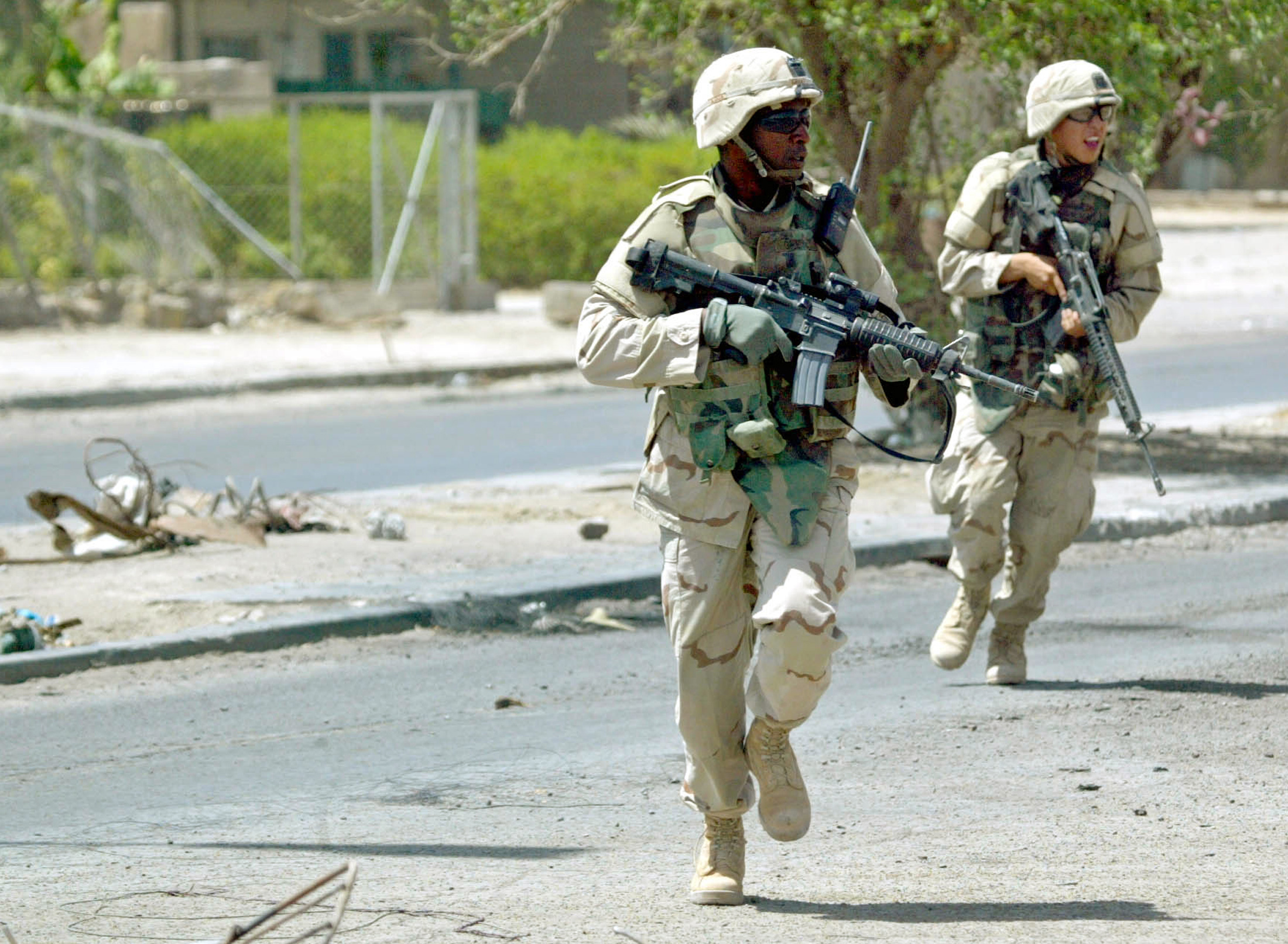 U.S. Army soldiers of the 1st Cavalry Division run across a street during a firefight in Sadr City on Aug. 18, 2004. Fighting between U.S. forces and Muqtada al-Sadr's Mehdi militia broke out in a Shiite slum in Baghdad. Photo by David P. Gilkey/Pool via Reuters