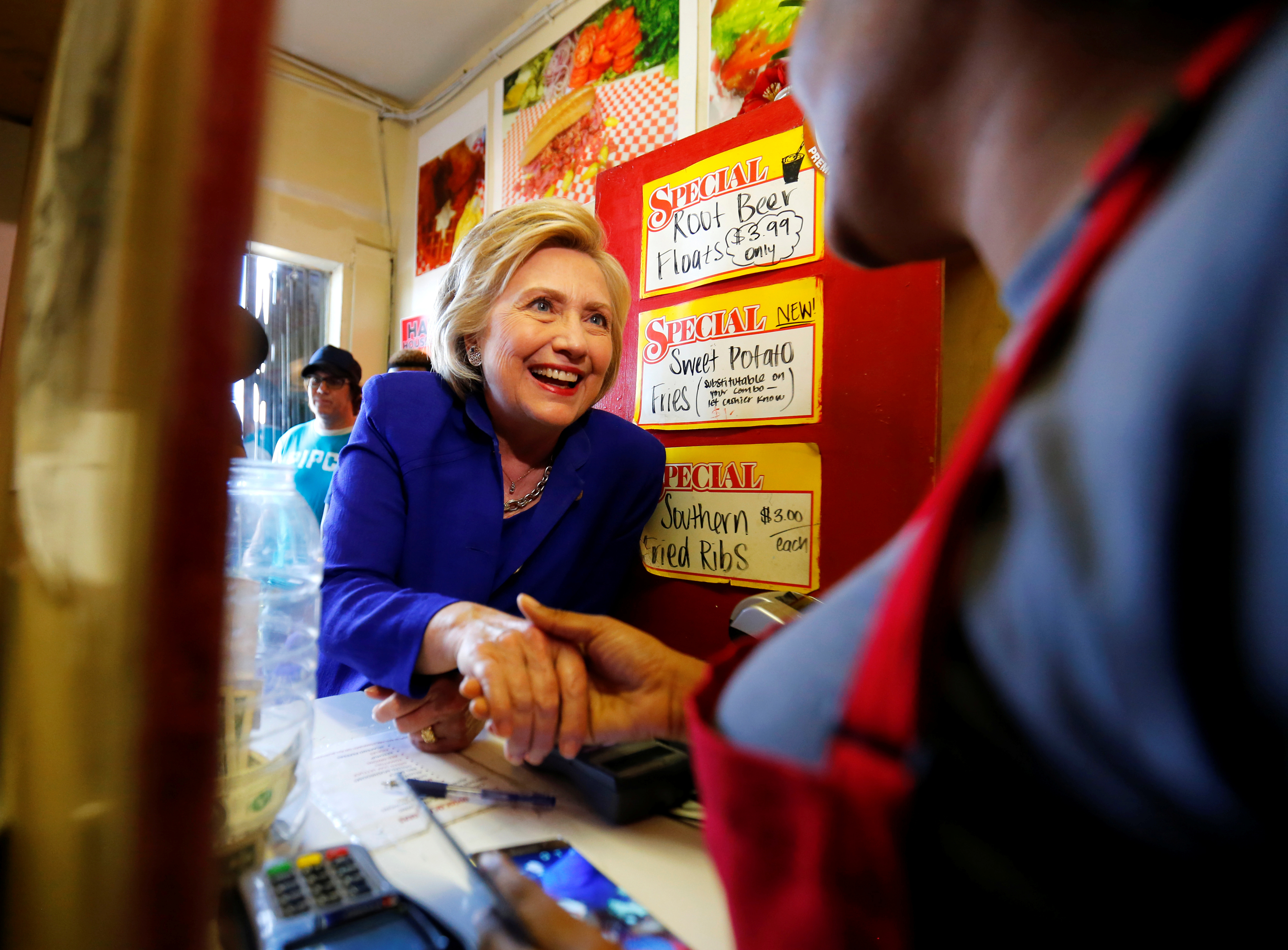 Demi Gibson, who works the order counter at Hawkins House of Burgers shakes hands with Hillary Clinton who made a lunchtime campaign stop a the restaurant in Watts, California. Photo by Mike Blake/Reuters