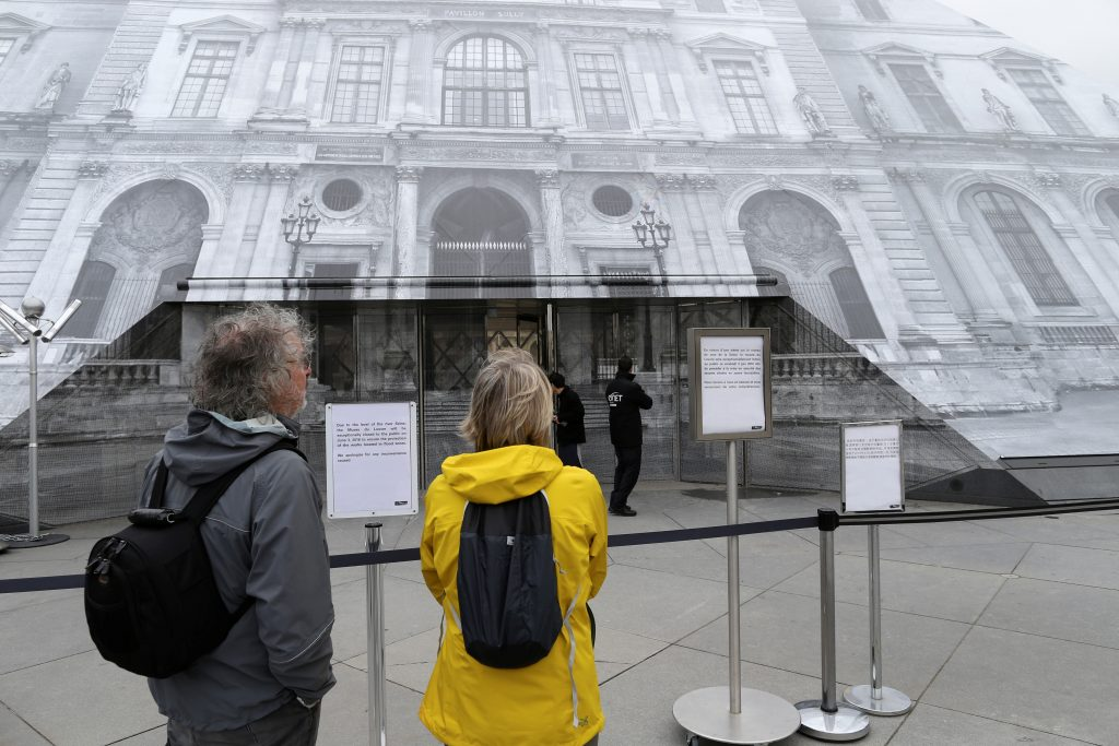 Tourists read information notices that indicate that the Louvre Museum is closed due to the rising Seine River in Paris, France, after days of almost non-stop rain caused flooding in the country, June 3, 2016. Photo By John Schults/Reuters