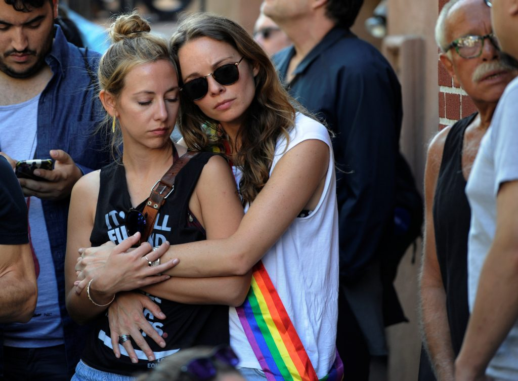Two women hold each other at a vigil outside The Stonewall Inn on Christopher Street, considered by some as the center of New York State's gay rights movement, following the shooting massacre at Orlando's Pulse nightclub, in the Manhattan borough of New York, U.S., June 12, 2016. Photo By Mark Kauzlarich/Reuters
