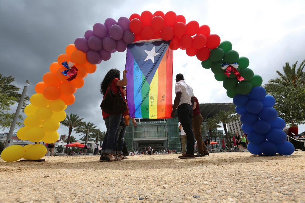 A Puerto Rican flag in rainbow colors and balloons are left at a makeshift memorial for the victims of the Pulse night club shooting in Orlando, Florida. Photo by Carlo Allegri/Reuters