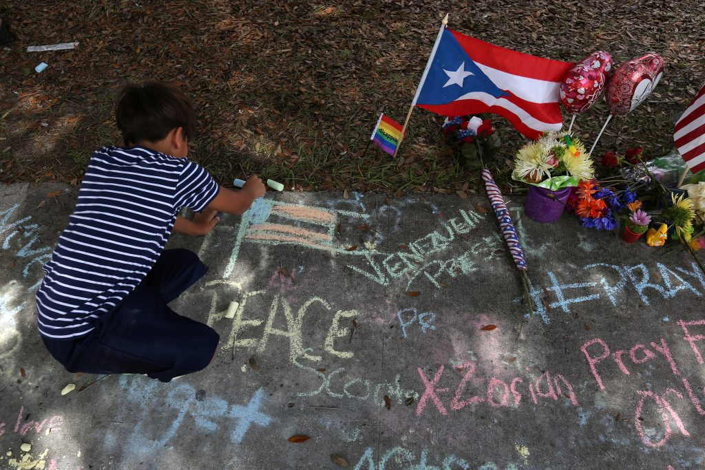 A child draws a U.S. flag on the sidewalk in chalk by a Puerto Rico flag at a makeshift memorial that is across the street from Pulse night club following last week's shooting in Orlando, Florida. Photo by Carlo Allegri/Reuters