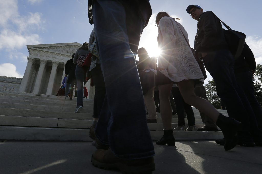 People wait in line in to be allowed in to watch arguments at the U.S. Supreme Court building on the first day of the court's new term in Washington, D.C. Photo by Jonathan Ernst/Reuters