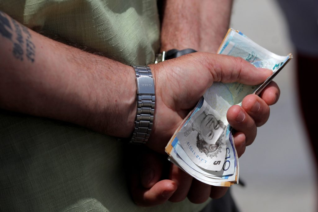A man holds various English Pound notes as he waits in line to exchange it for Euros notes outside a money exchange office in the British overseas territory of Gibraltar, historically claimed by Spain, June 24, 2016, after Britain voted to leave the European Union in the EU BREXIT referendum. Photo By Jon Nazca/Reuters