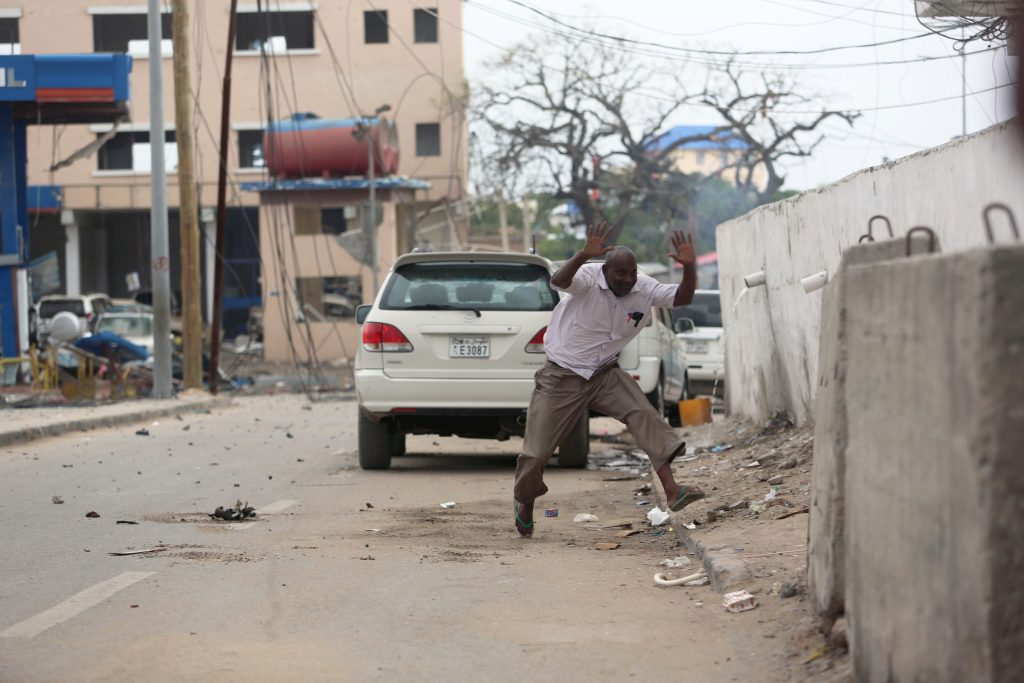 A man raises his hands as he runs from the scene of a suicide bomb attack outside Nasahablood hotel in Somalia's capital Mogadishu, June 25, 2016. REUTERS/Feisal Omar - RTX2I5V5