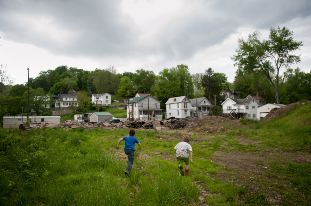 Children play in the field and rubble behind homes in Pomeroy, Ohio. Photo by Stephanie Strasburg/STAT