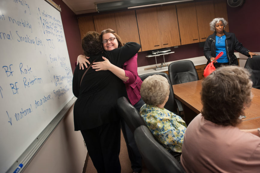Meigs County Health Department administrator Courtney Midkiff, in magenta, hugs Dr. Electra Paskett as the doctor arrives with her team for a meeting to discuss the Meigs County Cancer Initiative on Tuesday, May 3, 2016 at the health department in Pomeroy, Ohio.