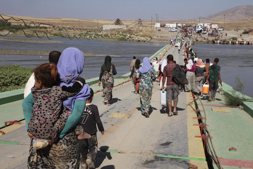 Displaced people from the minority Yazidi sect, fleeing the violence in the Iraqi town of Sinjar, re-enter Iraq from Syria at the Iraqi-Syrian border crossing in Fishkhabour, Dohuk Province, in 2014. Photo by Ari Jalal/Reuters