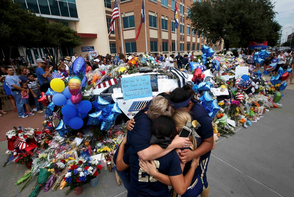 A softball team hugs after paying their respects at a makeshift memorial at Dallas Police Headquarters following the multiple police shootings in Dallas, Texas, U.S., July 9, 2016. Photo By Carlo Allegri/Reuters