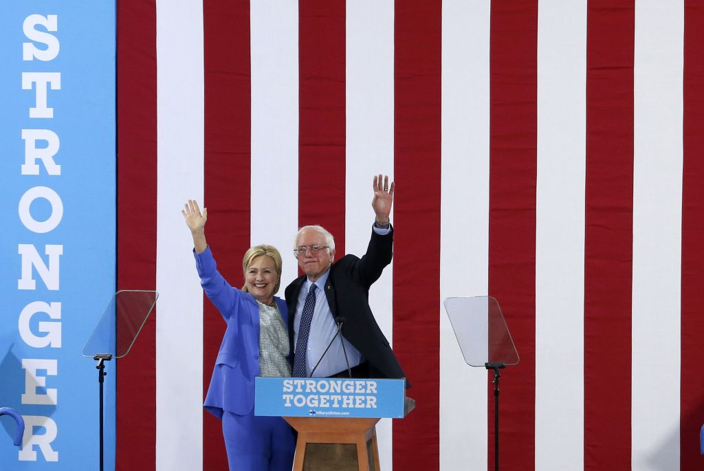 Presumptive Democratic presidential nominee Hillary Clinton and Bernie Sanders wave together during a campaign rally where Sanders endorsed Clinton in Portsmouth, New Hampshire. Photo by Mary Schwalm/Reuters