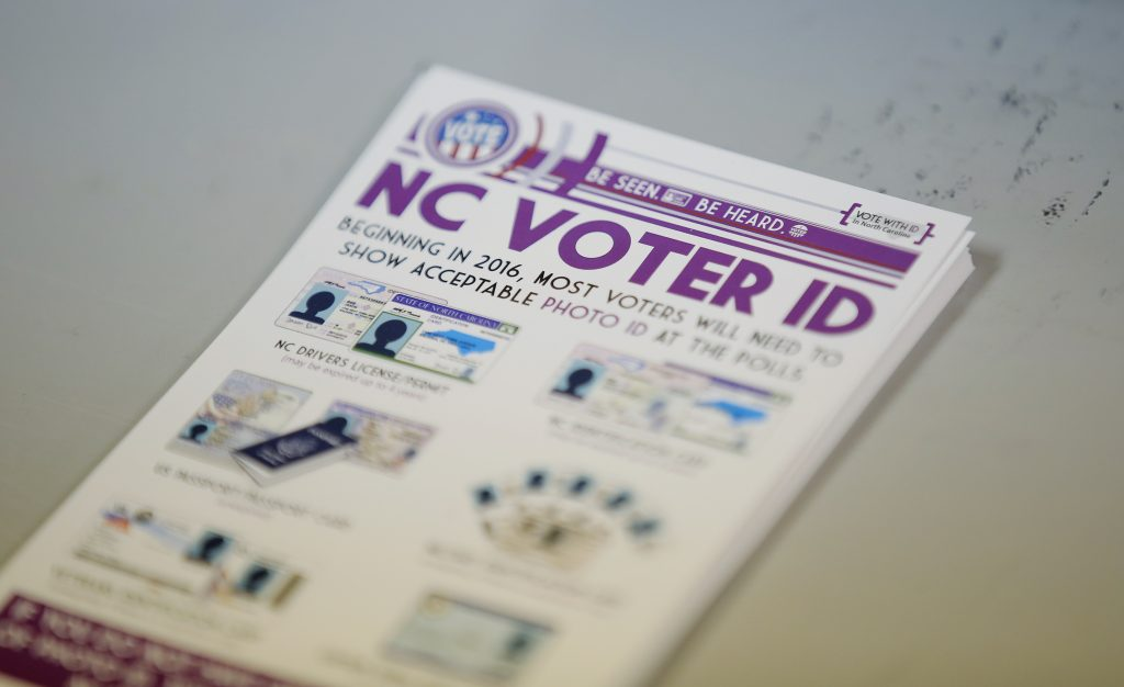 "A pile of government pamphlets explaining North Carolina's controversial ""Voter ID"" law sits on table at a polling station in Charlotte, North Carolina. Photo by Chris Keane/Reuters"