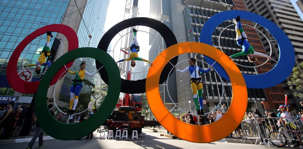 Acrobats perform on the Olympics rings at Paulista Avenue in Sao Paulo's financial center, Brazil, July 24, 2016. REUTERS/Paulo Whitaker - RTSJEYP