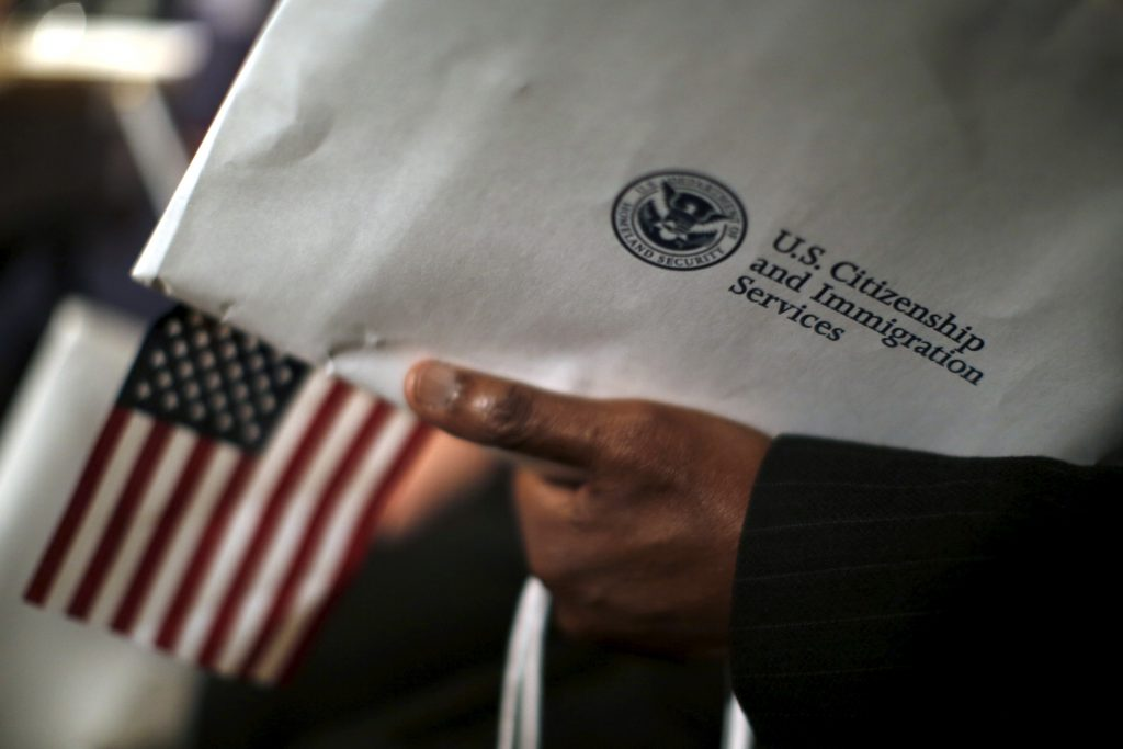 A man holds an envelope from the U.S. Citizenship and Immigrations Service during a naturalization ceremony at the National Archives Museum in Washington, D.C., in December 2015. Carlos Barria/Reuters