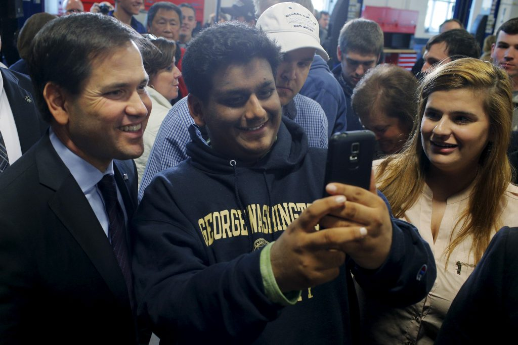 U.S. Republican presidential candidate and U.S. Senator Marco Rubio poses for a selfie with an audience member at a campaign town hall meeting at Nashua Community College in Nashua, New Hampshire January 7, 2016. REUTERS/Brian Snyder - RTX21GZX