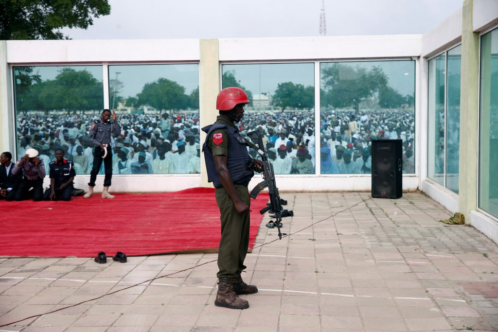 A policeman stands guard as Muslims attend the Eid al-Fitr prayers at Kofa Mata praying ground in Nigeria's northern city of Kano on July 6. Photo by Akintunde Akinleye/Reuters