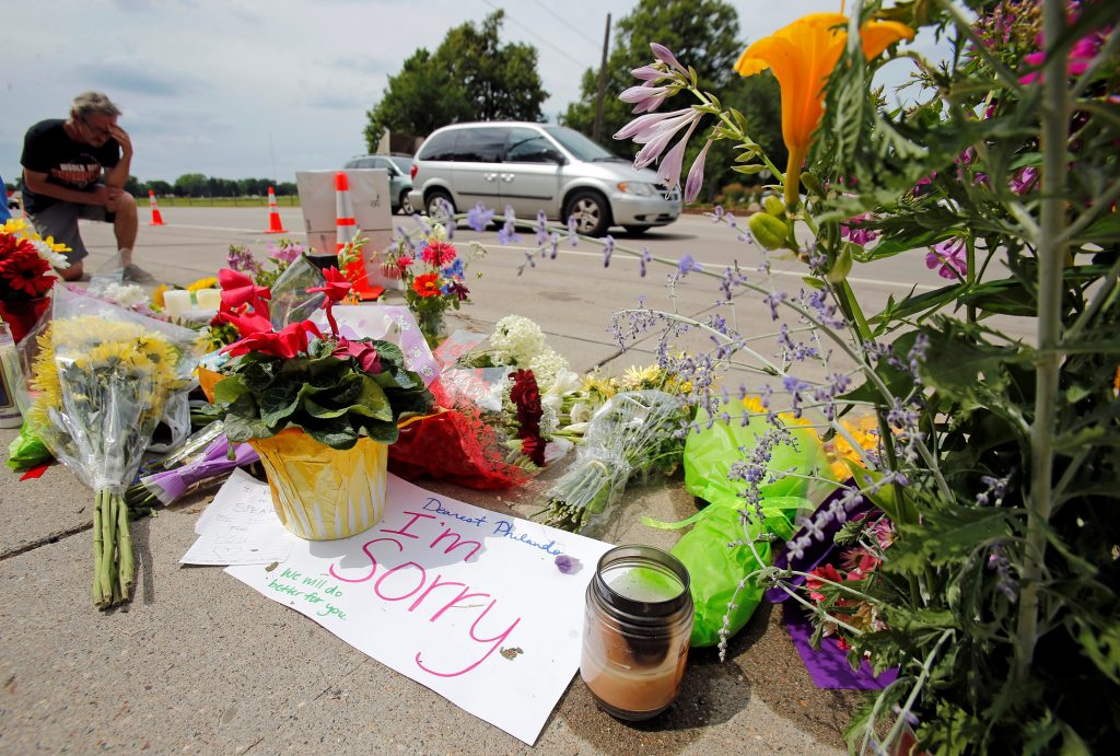 A man kneels at a make-shift memorial at the site of the police sho…