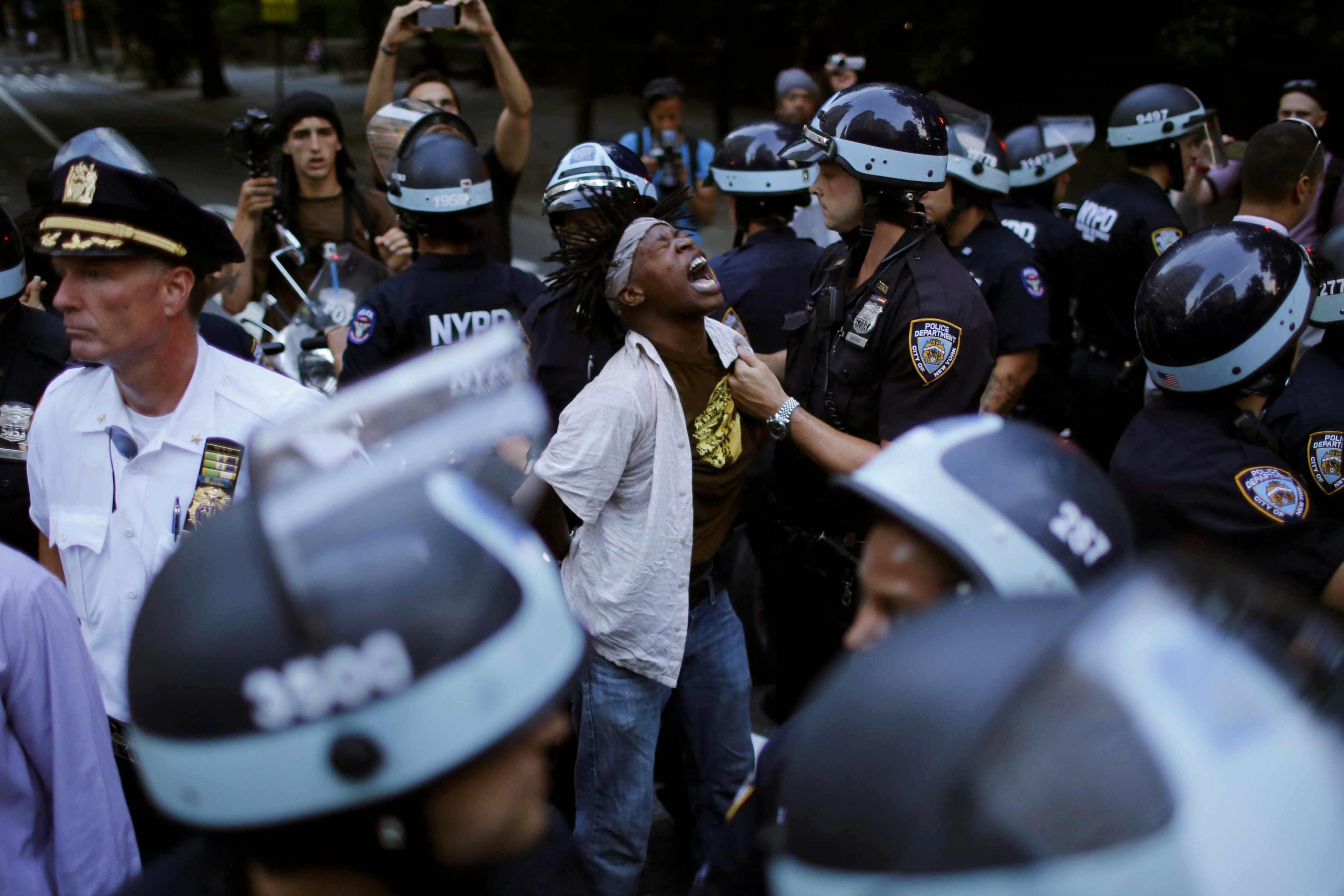 A protester is detained by NYPD officers as people protest the killing of Alton Sterling and Philando Castile during a march in New York City. Photo by Eduardo Munoz/Reuters.
