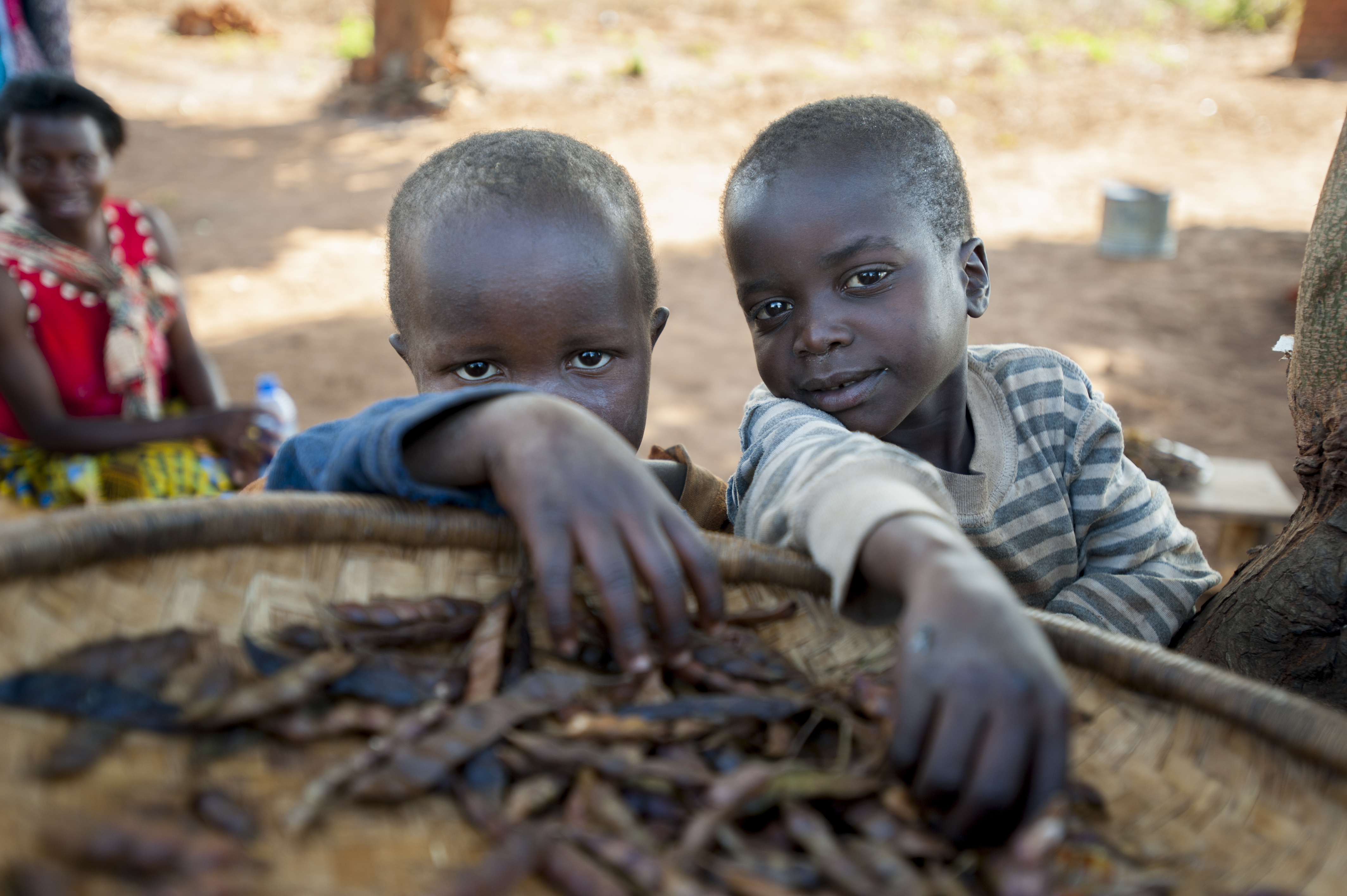"""The boys, Innocent and Kelvin, reach for some dried peas called """"nandoko."""" Photo by Sebastian Rich for UNICEF"""