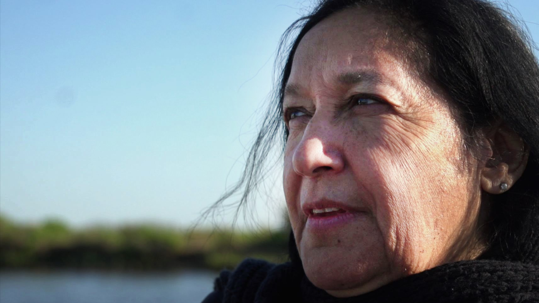 Theresa Dardar, pictured here in 2012, belongs to the Point Au Chien tribe in coastal Louisiana. She's lived here all her life. When PBS NewsHour visited four years ago, she showed us a cemetery she could once access by land -- now, she has to travel there by boat. Today, the encroaching water is worse. Photo by PBS NewsHour
