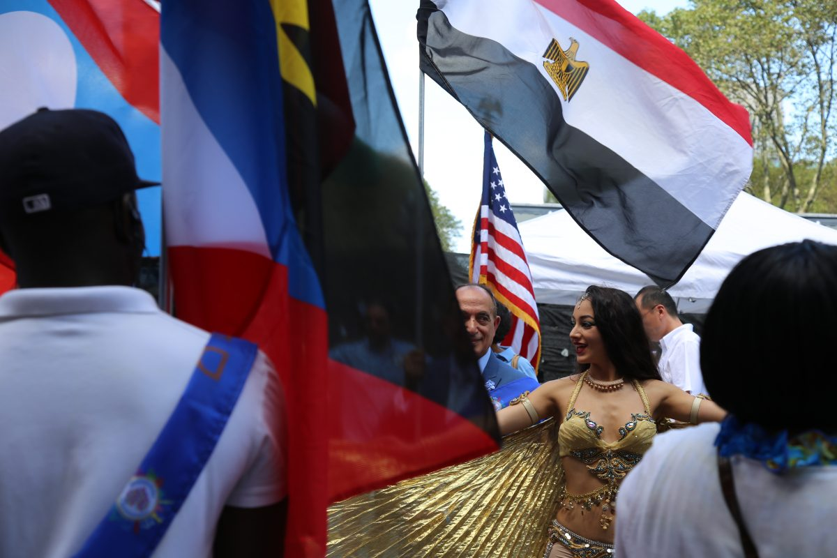 A woman dances underneath the flag of Egypt during the 3rd annual International Day of Friendship celebration in Brooklyn, NY, on August 7, 2016. Photo by Omar Etman/PBS NewsHour Weekend