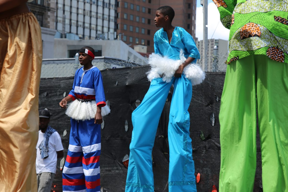 Boys do the moko jumbie, a stilt walking dance native to Trinidad and Tobago, at the 3rd annual International Day of Friendship celebration in Brooklyn, NY on August 7, 2016. Photo by Omar Etman/PBS NewsHour Weekend