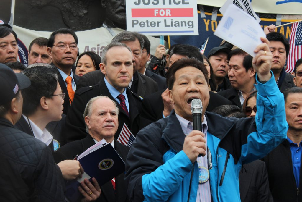 Phil Gim, a community activist, spoke at the protest over conviction of former NYPD officer Peter Liang in New York, urging people to register to vote.