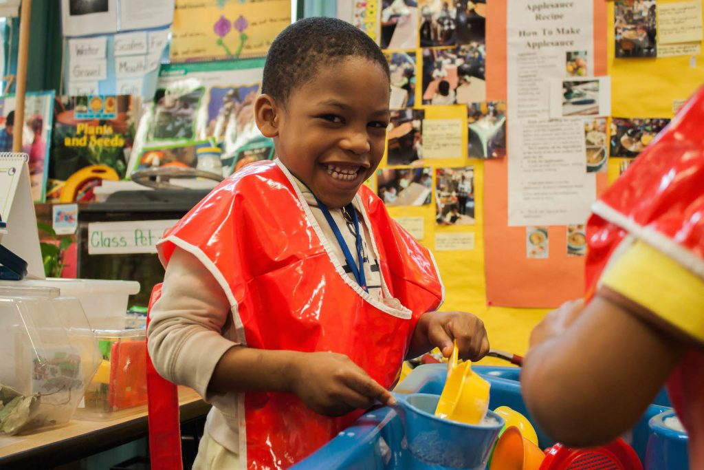 Preschool student Josiah Taft, a student in Dasarie Forde's class at P.S. 3 in Brooklyn, practices washing a doll as part of the unit on babies. June 17, 2016. Photo by Jamie Martines