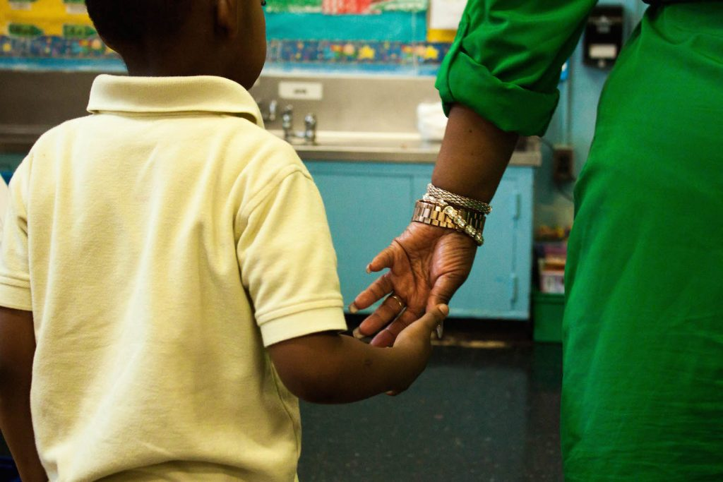 A preschool student reaches for the hand of his teacher, Dasarie Forde, at P.S. 3 in Brooklyn. Photo by Jamie Martines
