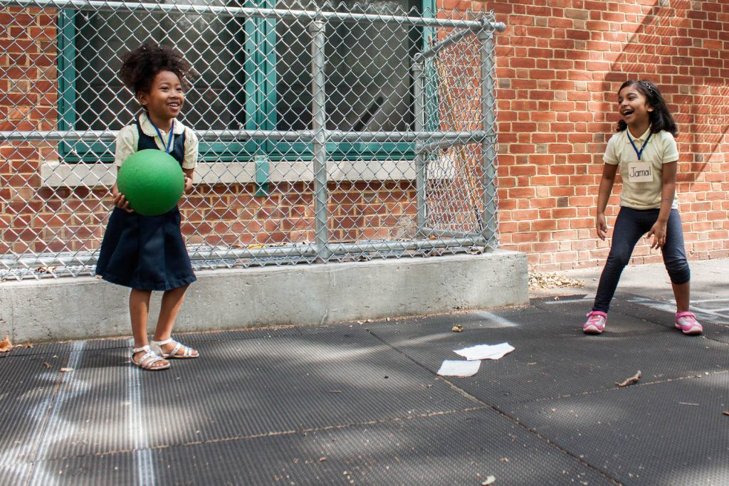 Preschool students in Dasarie Forde's class at P.S. 3 in Brooklyn, Deanna Moody (left) and Jamal Sidratul (right), play during structured outdoor playtime. June 17, 2016. Photo by Jamie Martines
