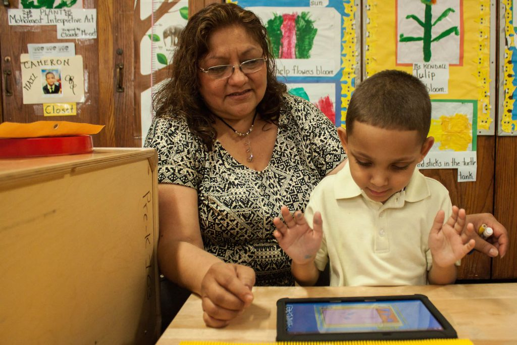 A student works with an assistant teacher to use a tablet during an activity to practice matching and identifying shapes. June 17, 2016. Photo by Jamie Martines