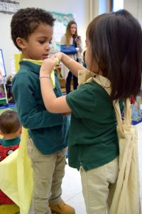 Jamie Huynh, 4, ties a cape on her classmate, Gabriel Monteiro, 4, in their public preschool class at a Boston elementary school. The capes were inspired by a book called Nana in the City in which a little boy wears a cape to help him be brave in a new place. Photo by Lillian Mongeau / Hechinger Report