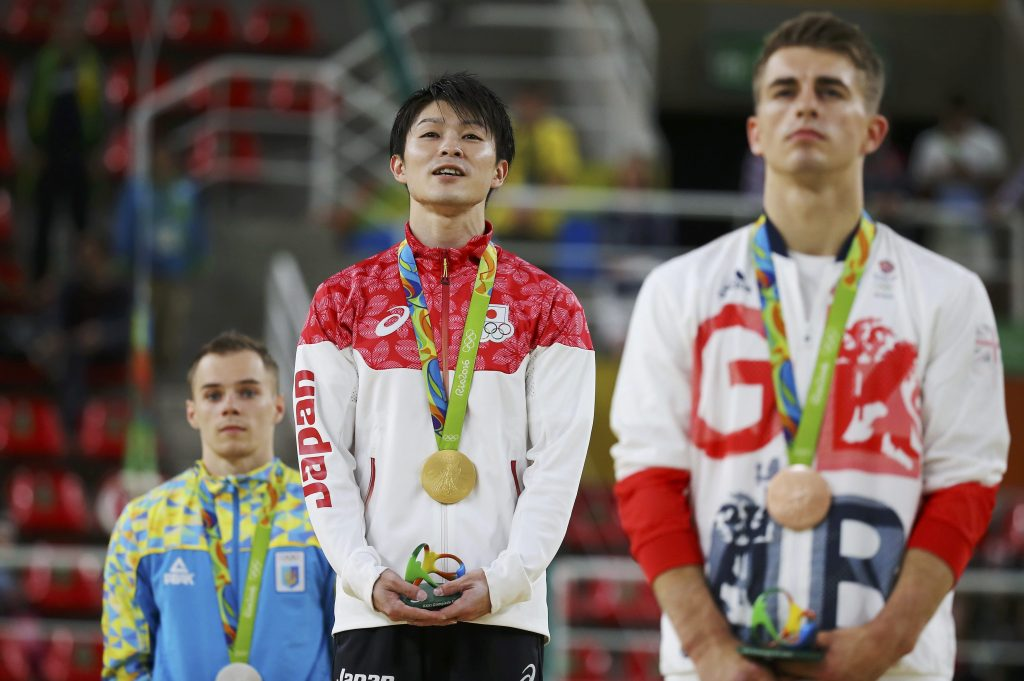 Gold medallist Kohei Uchimura of Japan (C) on the podium with silver medallist Oleg Verniaiev of Ukraine (L) and bronze medallist Max Whitlock of United Kingdom (R) after the men's individual all-around final. Photo by Damir Sagolj/Reuters
