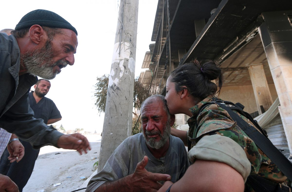 A Syria Democratic Forces (SDF) fighter comforts a civilian who was evacuated with others by the SDF from an Islamic State-controlled neighbourhood of Manbij, in Aleppo Governorate, Syria, August 12, 2016. The SDF has said Islamic State was using civilians as human shields. REUTERS/Rodi Said TPX IMAGES OF THE DAY - RTSMZ59