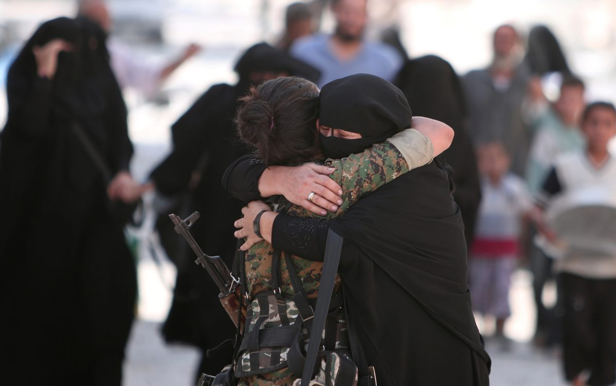 A woman embraces a Syria Democratic Forces (SDF) fighter after she was evacuated with others by the SDF from an Islamic State-controlled neighbourhood of Manbij, in Aleppo Governorate, Syria, August 12, 2016. The SDF has said Islamic State was using civilians as human shields. REUTERS/Rodi Said - RTSMZ6D