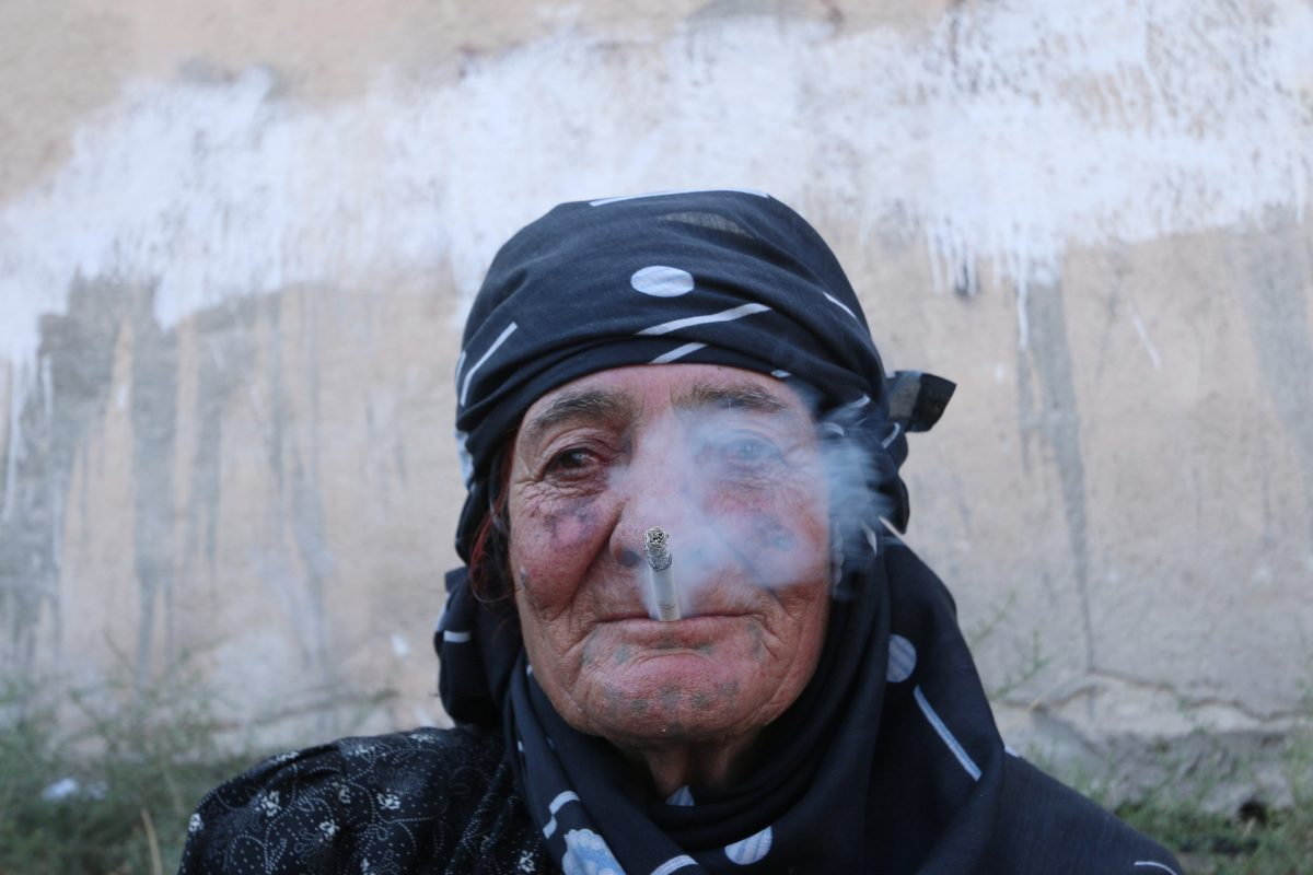 A woman smokes as she rests after she was evacuated with others by the Syria Democratic Forces (SDF) fighters from an Islamic State-controlled neighbourhood of Manbij, in Aleppo Governorate, Syria, August 12, 2016. The SDF has said Islamic State was using civilians as human shields. REUTERS/Rodi Said - RTSMZN0