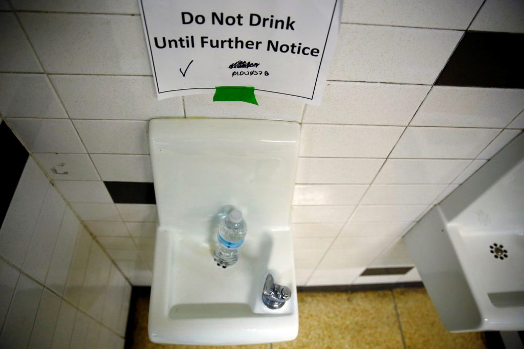 A sign is seen next to a water dispenser at North Western High School in Flint, a city struggling with the effects of lead-poisoned drinking water in Michigan, May 4, 2016. Photo By Carlos Barria/Reuters