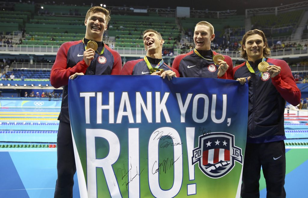 Gold medalists Michael Phelps, Cody Miller, Nathan Adrian and Ryan Murphy of USA pose with a banner.  Photo by Stefan Wermuth/Reuters