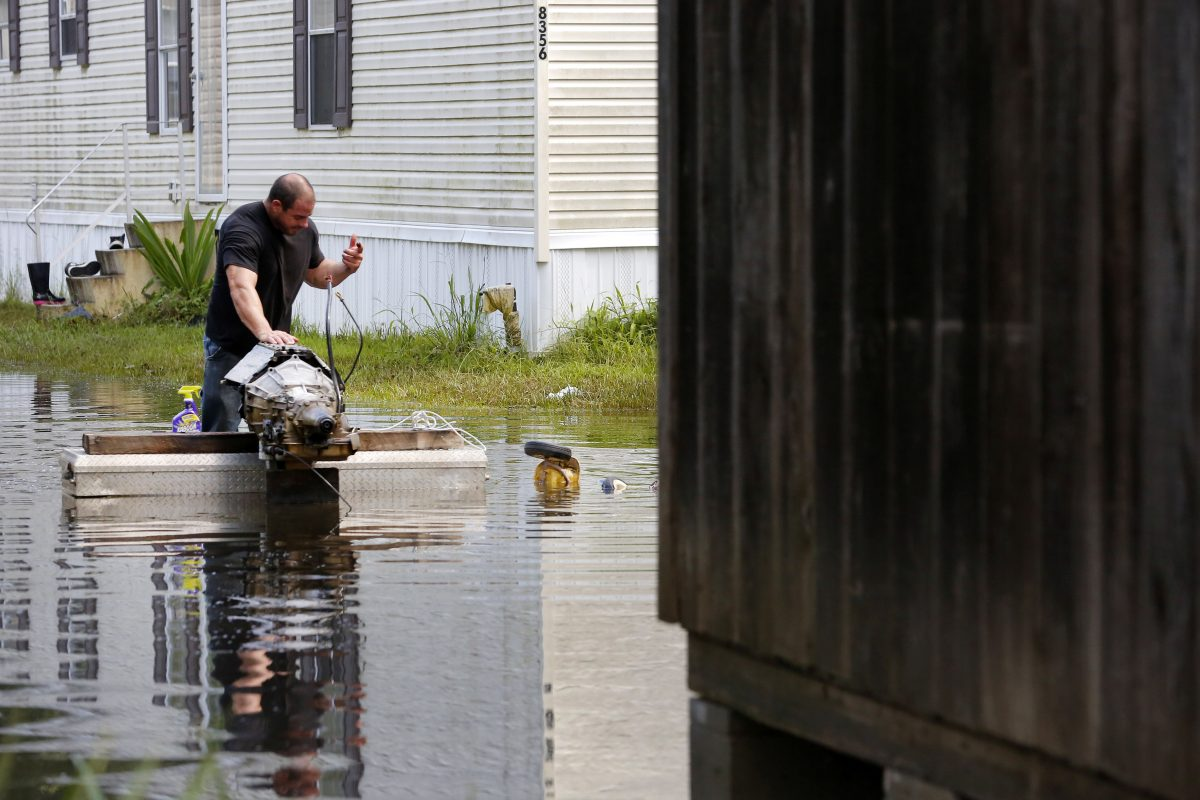 Jason LeBlanc tries to salvage a flood damaged motor outside of his house in Sorrento, Louisiana, U.S., August 20, 2016. REUTERS/Jonathan Bachman - RTX2MB6B