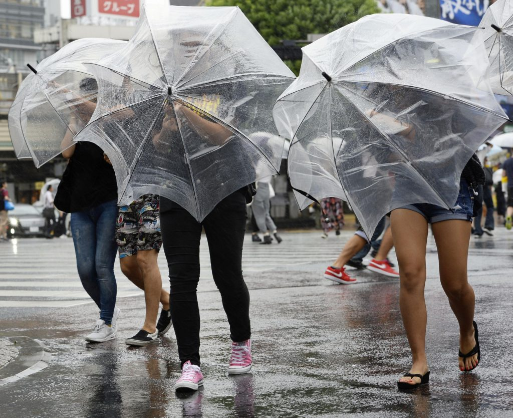 Pedestrians walk under heavy rain and wind in Tokyo, Japan, in this photo taken by Kyodo August 22, 2016. Mandatory credit Kyodo/via REUTERS