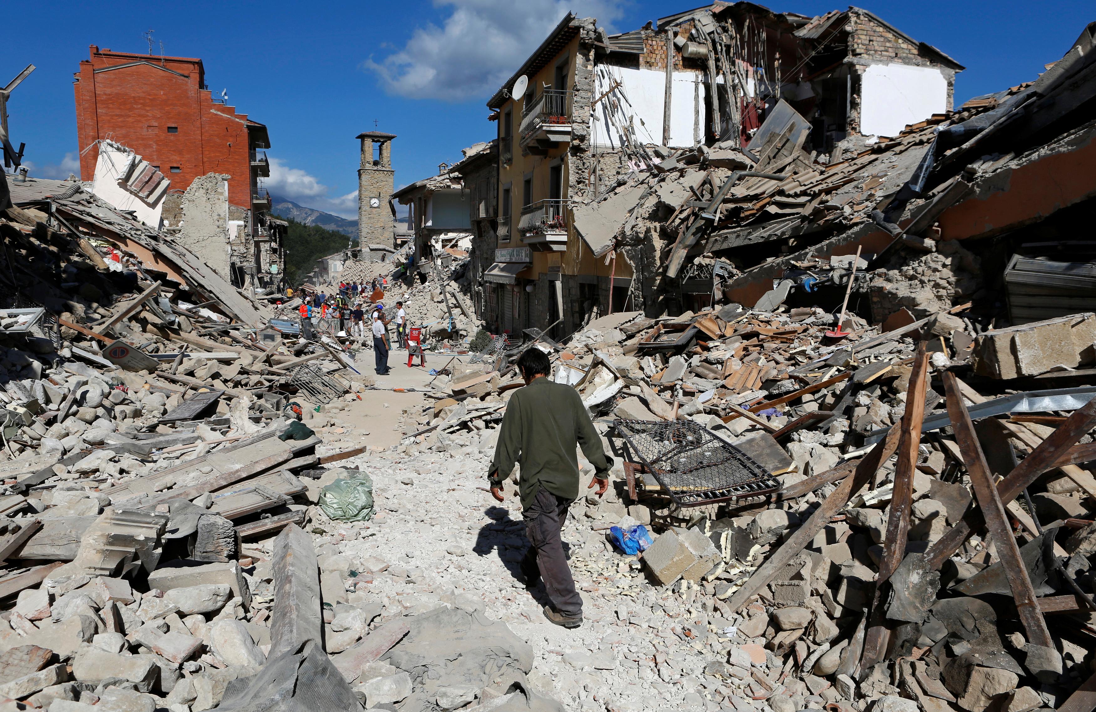 A man walks through the rubble following a 6.2-magnitude earthquake in Pescara del Tronto. Photo by Remo Casilli/Reuters
