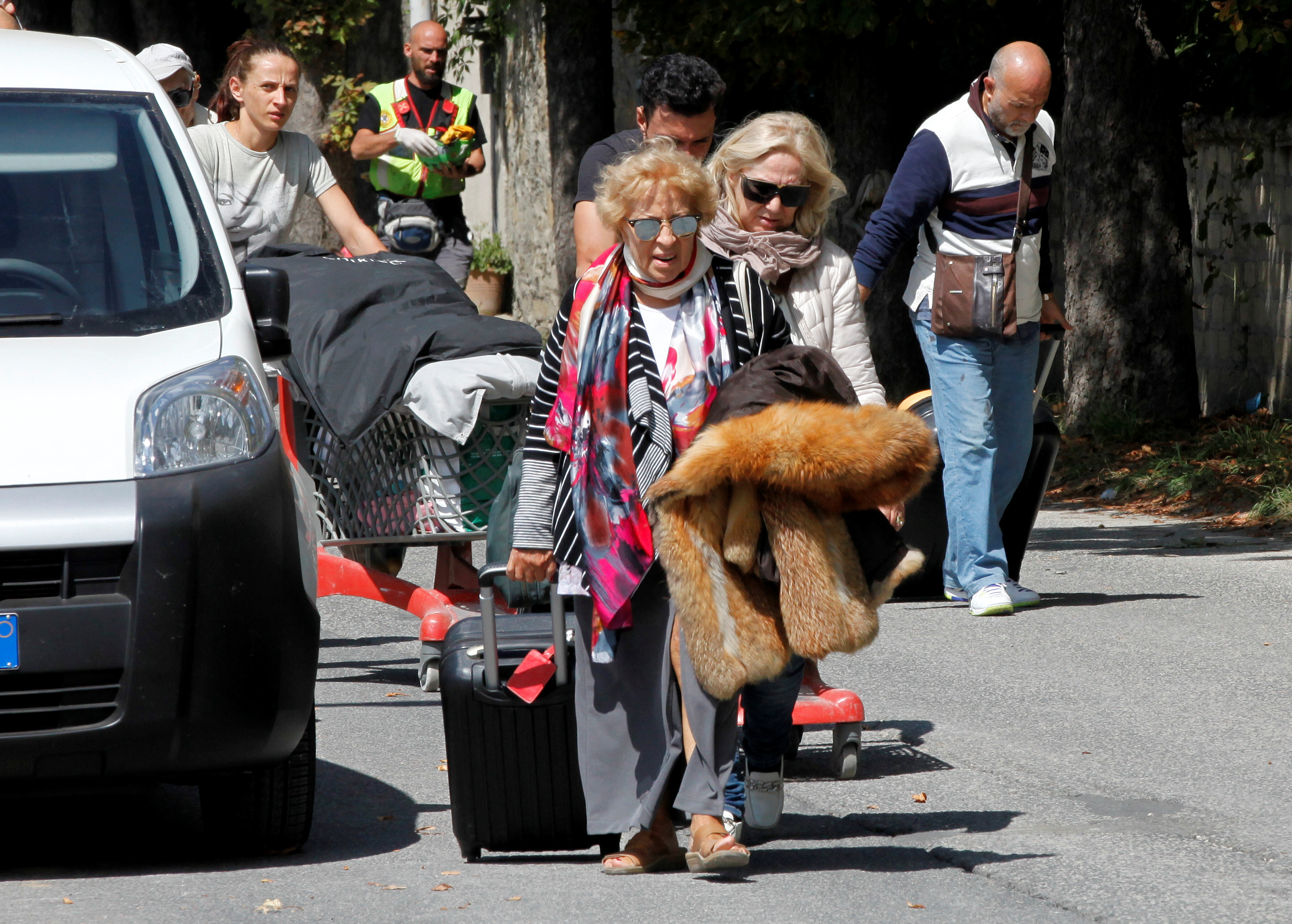People walk with their belongings following an earthquake in Amatrice, central Italy. Photo by Ciro De Luca/Reuters