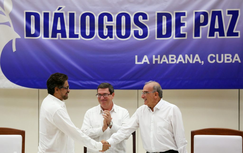 Colombia's FARC lead negotiator Ivan Marquez (left) and Colombia's lead government negotiator Humberto de la Calle (right) shake hands while Cuba's Foreign Minister Bruno Rodriguez looks on, after signing a final peace deal in Havana, Cuba, on Aug. 24. Photo by Alexandre Meneghini/Reuters