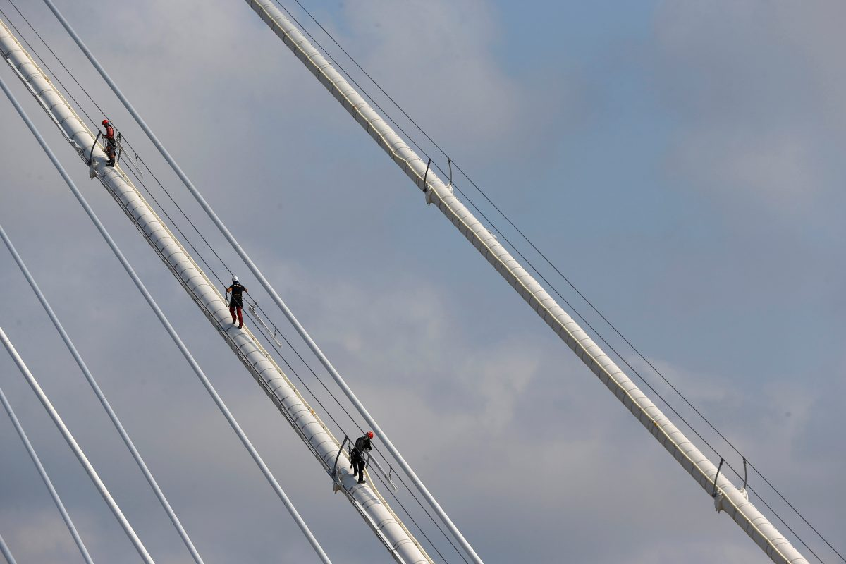 Workers climb up to a tower of the Yavuz Sultan Selim Bridge, the third Bosphorus bridge linking the European and Asian sides of Istanbul, Turkey, August 23, 2016. Picture taken August 23, 2016. REUTERS/Osman Orsal - RTX2N6J4
