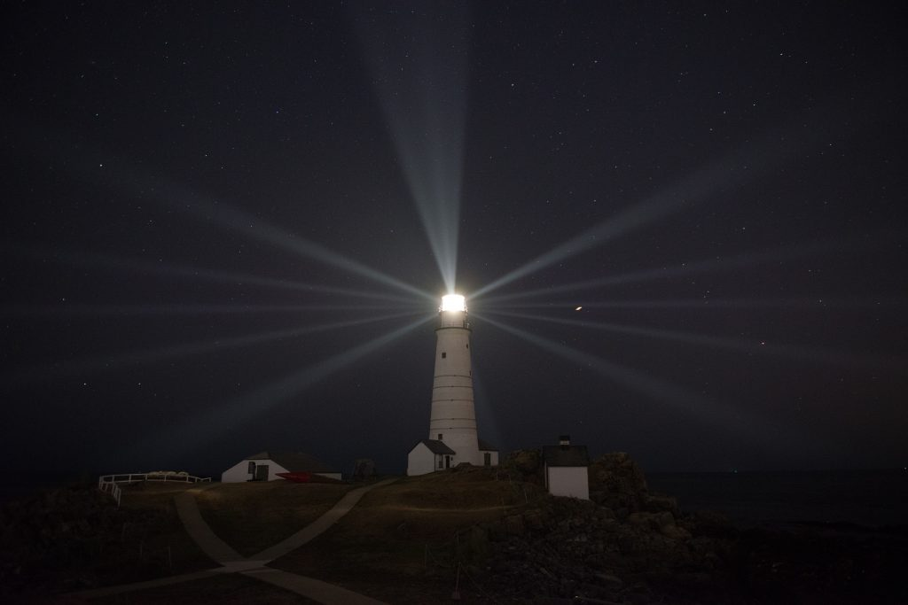 Boston Light's beams of light radiate across the night sky. Photo by: Class Andrew Barresi/U.S. Coast Guard
