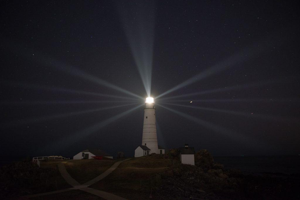 Boston Light's beams of light radiate across the night sky. Photo by: Class Andrew Barresi/U.S. Coast Guard