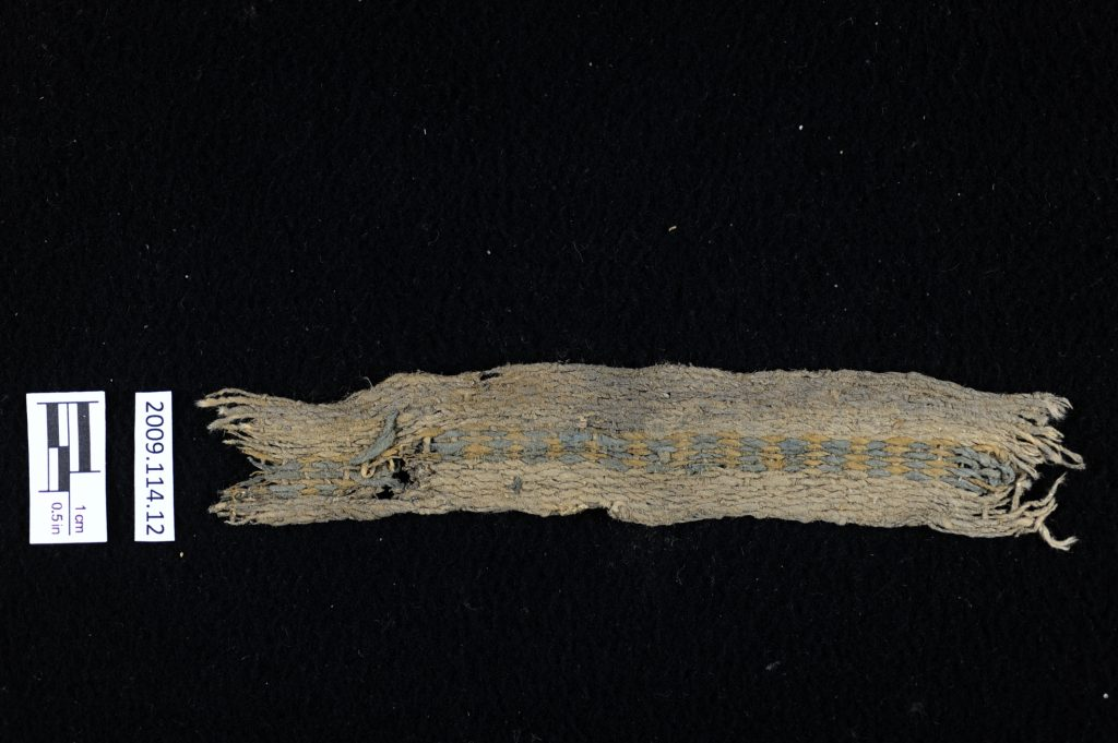 6,000-year-old, all-cotton band made of warp-faced plain-weave band with a decorative stripe down the center that is two-color complementary-warp weave in indigo blue and gold iron oxide (ochre). Photo by Lauren Urana