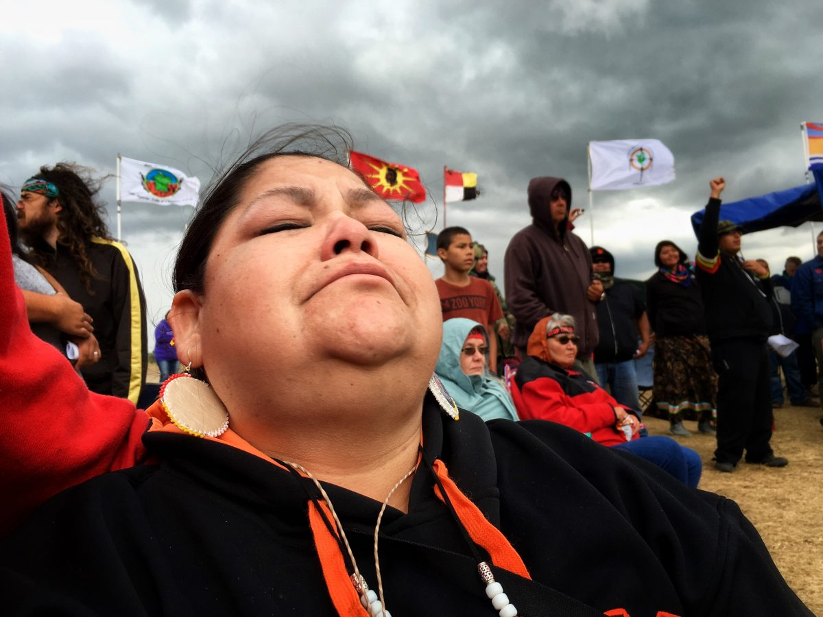 Andrea Longoria (Cheyenne Arapaho / Caddo) fights off tears of joy after learning that construction of the $3.8 billion dollar Dakota Access Pipeline will not be permitted to be built on land belonging to the Army Corps of Engineers and that borders the Standing Rock Sioux Indian Reservation. Photo by Jenni Monet