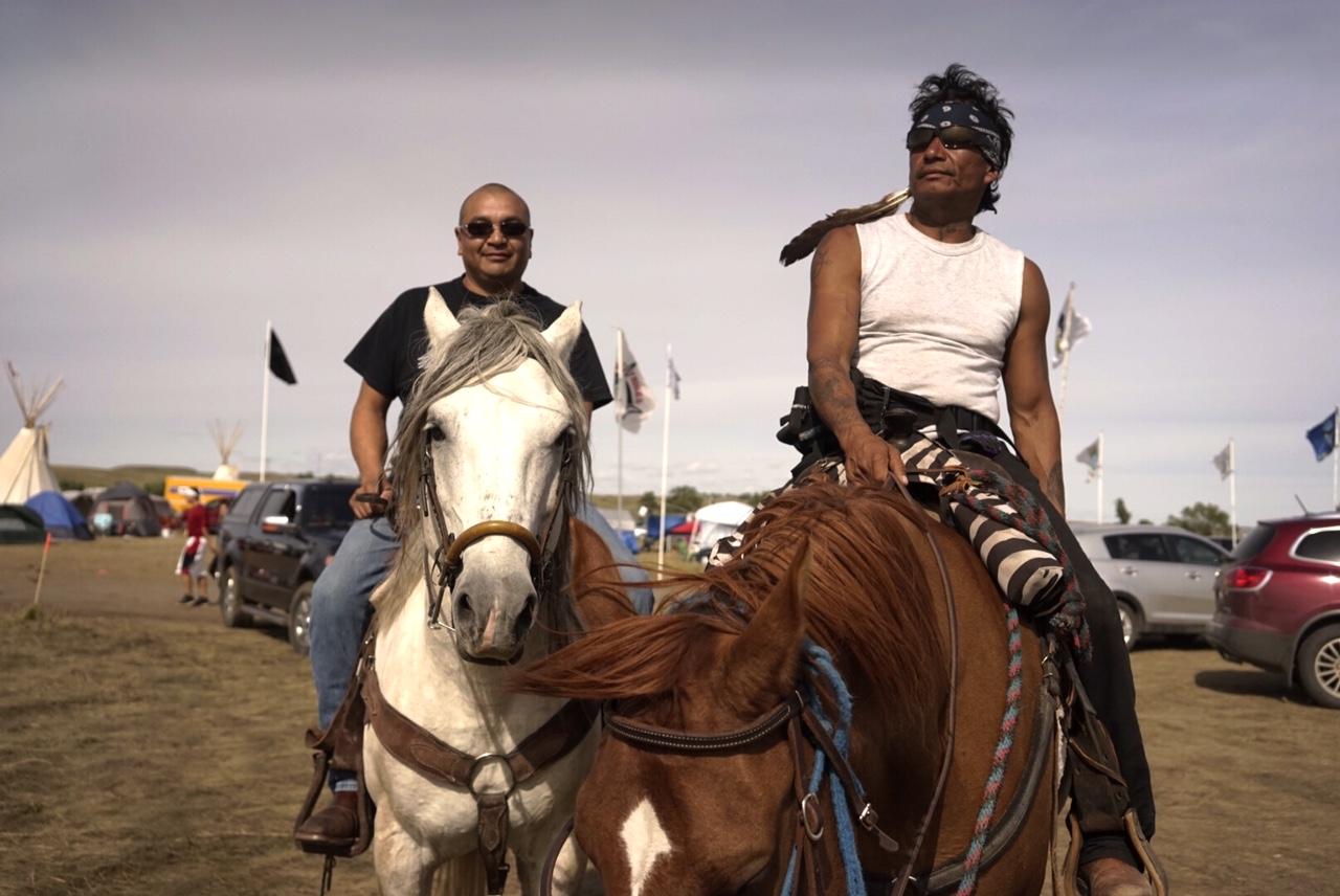 "Two members of the Standing Rock tribe riding through the growing protest camp where hundreds and hundreds of people from tribes all over North America are coming to join Standing Rock's protest against an oil pipeline that they say will destroy some of their sacred lands and potentially contaminate their water supply. When I asked if these big crowds would stick around, the man on the left said ""Oh yeah... We're building our shelters for winter right now."" Photo by William Brangham"