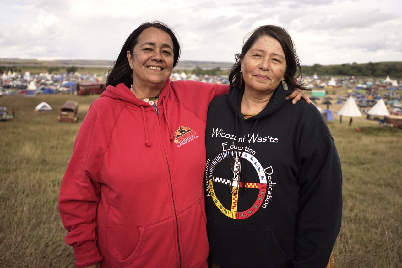 Leslie White Temple-Gipp (right) and her friend, Diench, stand atop the hill overlooking the sprawling protest camp. Photo by William Brangham